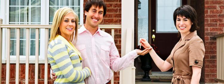 A man and woman standing in front of their new house, receiving keys from their realtor.