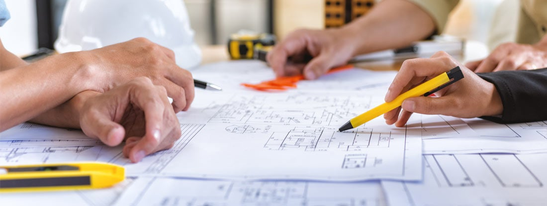 Architect checks construction blueprints on new project with tools at desk in office.