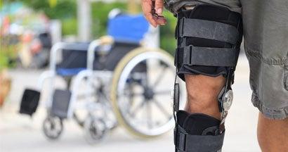 Senior man wear knee support brace on leg standing near wheelchair