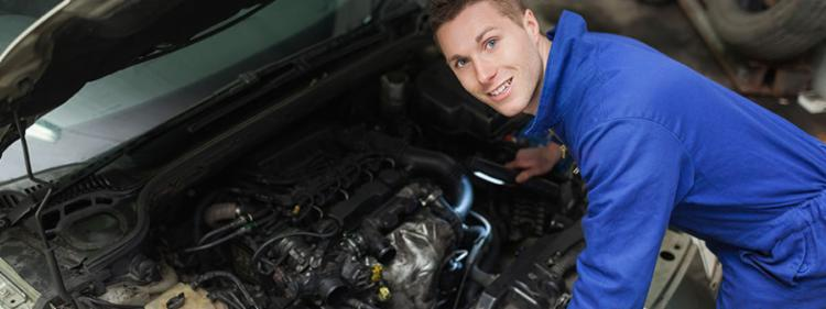 Mechanic looking under the hood of a car and smiling.