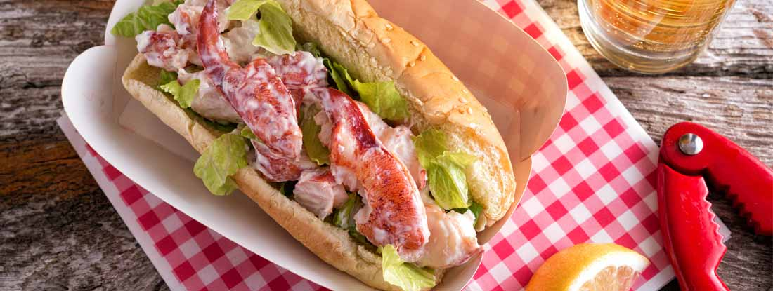 A delicious lobster roll on a rustic wood table top