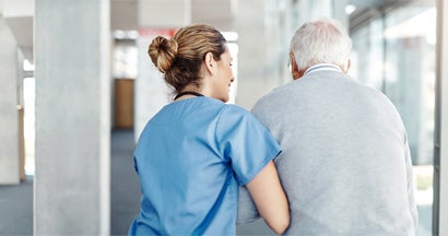 Female nurse assisting her senior patient while walking