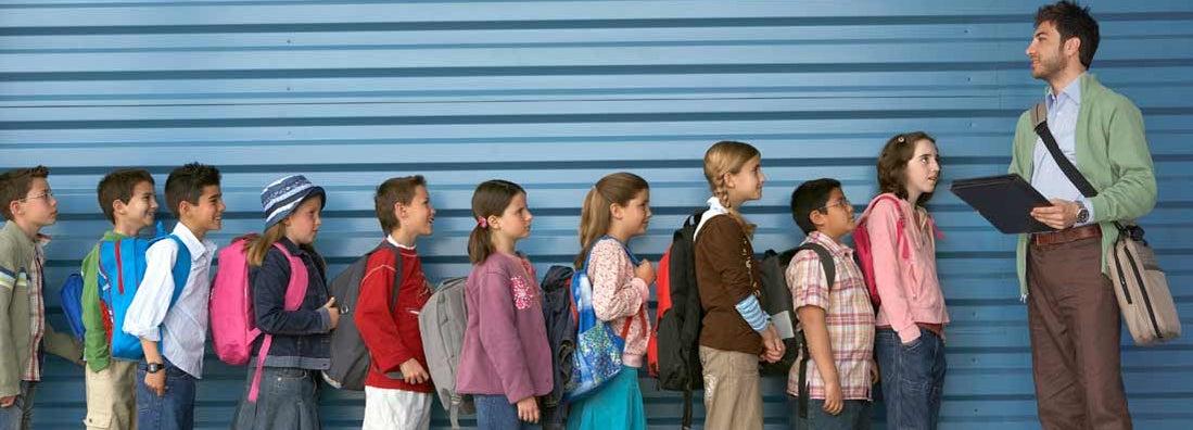 Male teacher by row of children