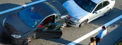 Two cars sit alongside a road following a traffic collision.