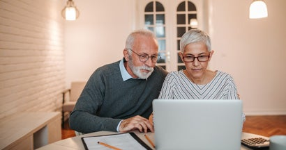 Senior couple researching long term care insurance taxes together