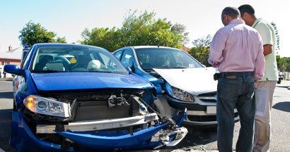 Two men conferring next to car accident. What happens if an at-fault driver doesn't have insurance.