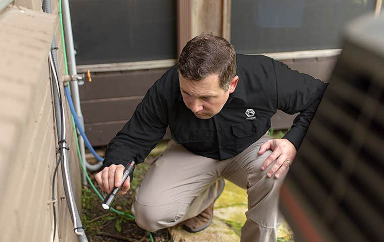 technician inspecting around a house