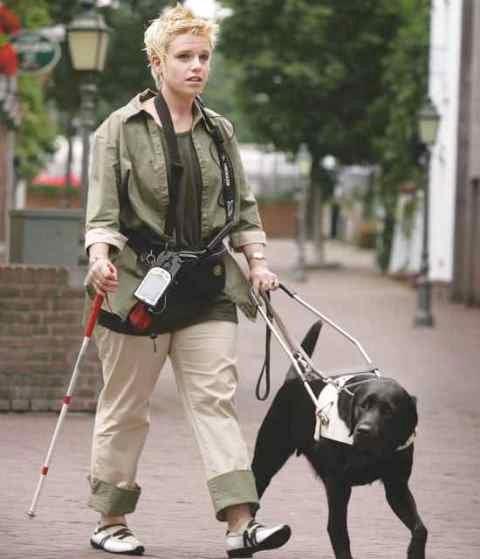 Jonge blinde vrouw met  geleidenhond teste de iCane.