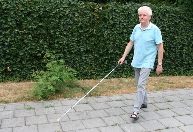 Columnist Wim Pierik loopt met zijn geleidestok over het trottoir.