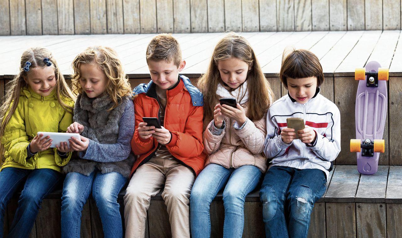 kinderen kijken op mobieltje