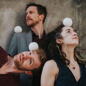 Drie artiesten jongleren met wit balletje.