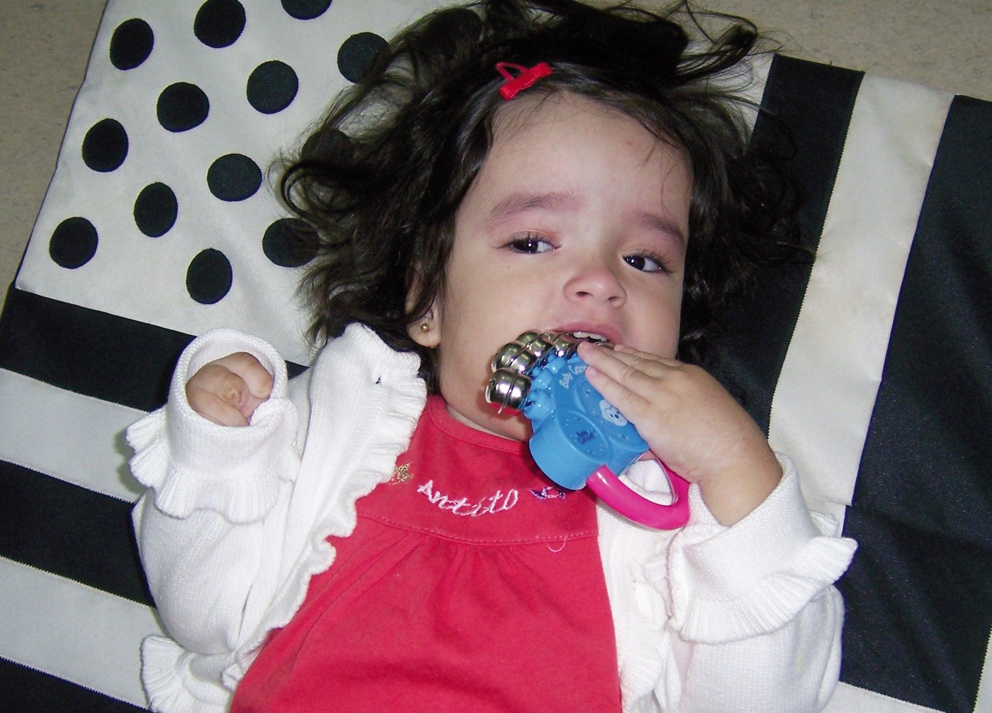 Slechtziende meisje van ongeveer 2 jaar ligt op een contrastrijk kleed en bijt op een rammelaar met belletjes.
