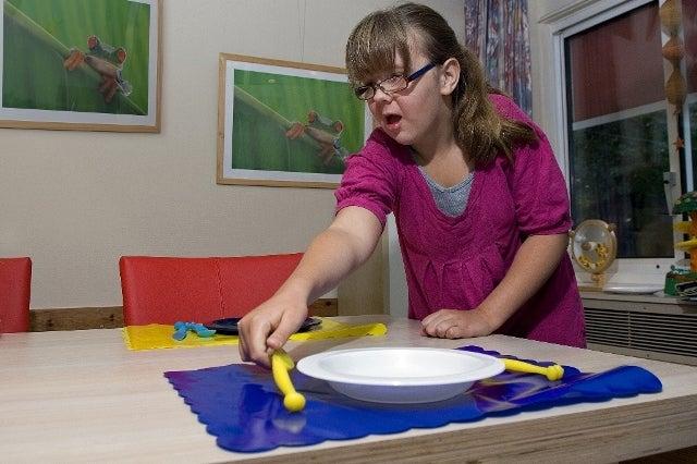 Jonge vrouw met visuele en verstandelijke beperking dekt de tafel met contrastrijke attributen.