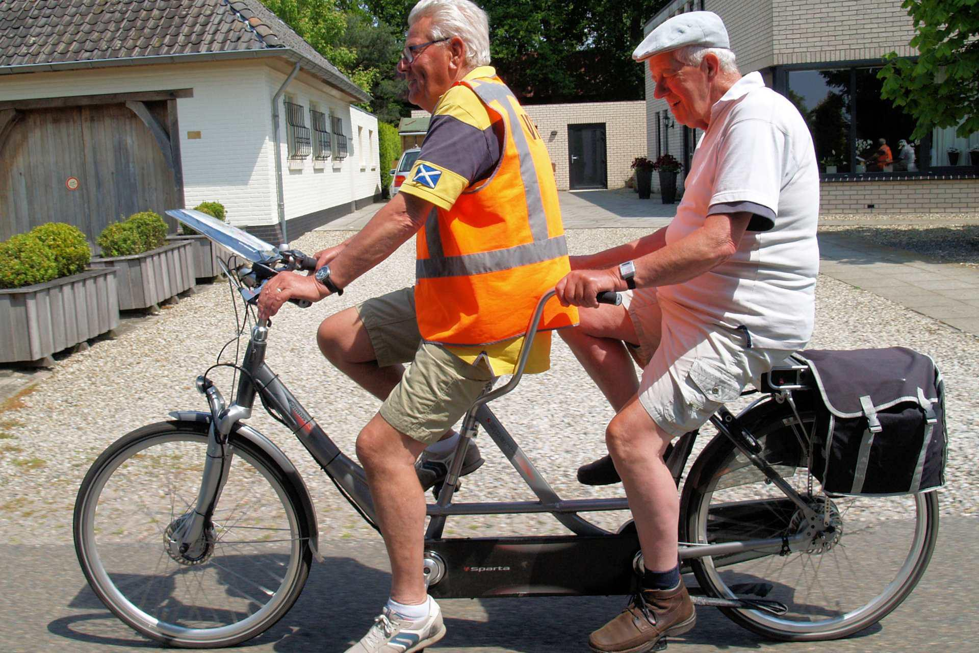 Twee heren fietsen op een tandem met op de achtergrond een huis