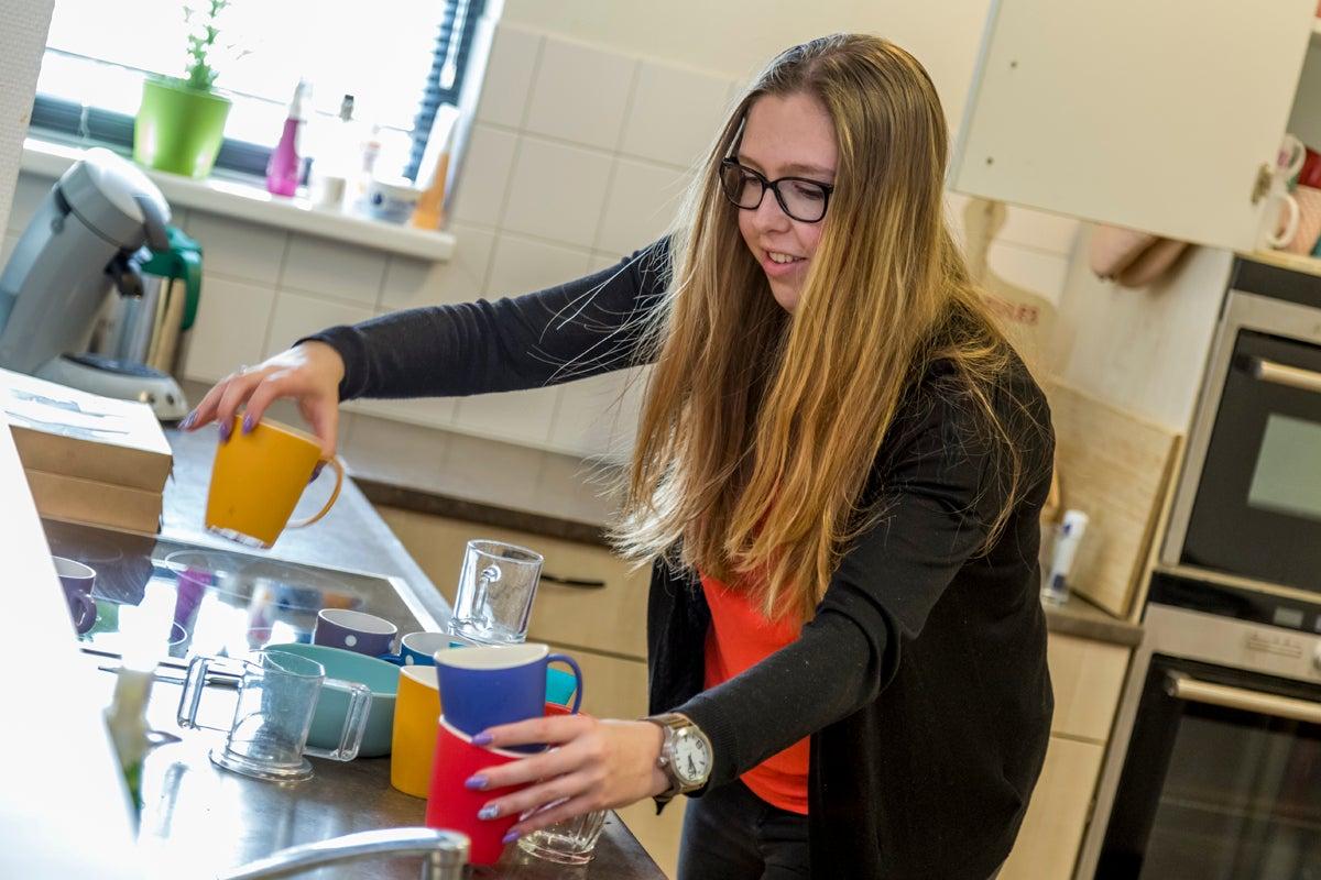 Stagiaire Nikki druk bezig met kopjes opruimen in de keuken.