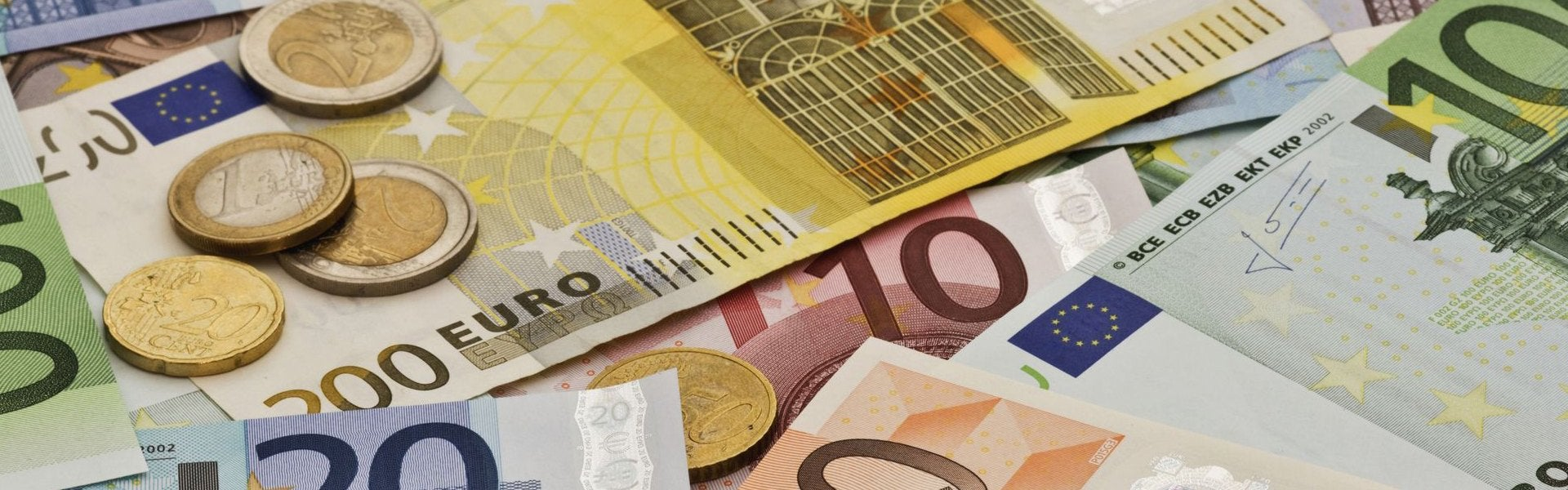 Afbeelding van enkele papieren geldbiljetten en munten.