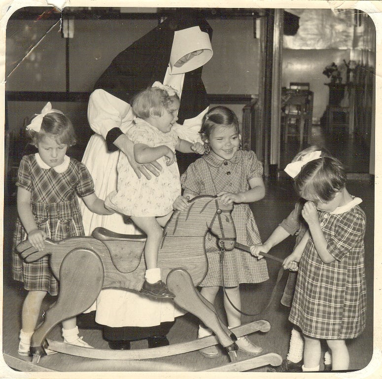Zuster met vijf blinde kleuters en een hobbelpaard. Rond 1950.