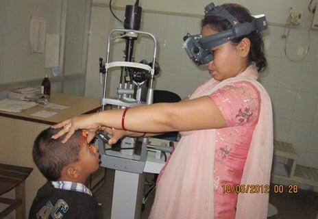 Nepalese oogarts onderzoek jongetje in basisschoolleeftijd met een lampje en een hoofdbril.
