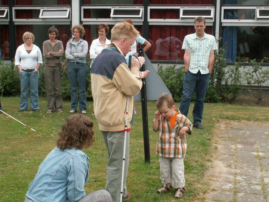 Blinde kleuter luistert naar het geluid van handenklap door de instructeur