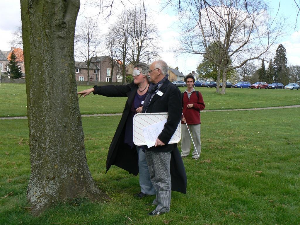 Dame met simulatiebril staat met begeleider bij een boom om te oefenen met echolocalisatie. Op de achtergrond Dan Kish.