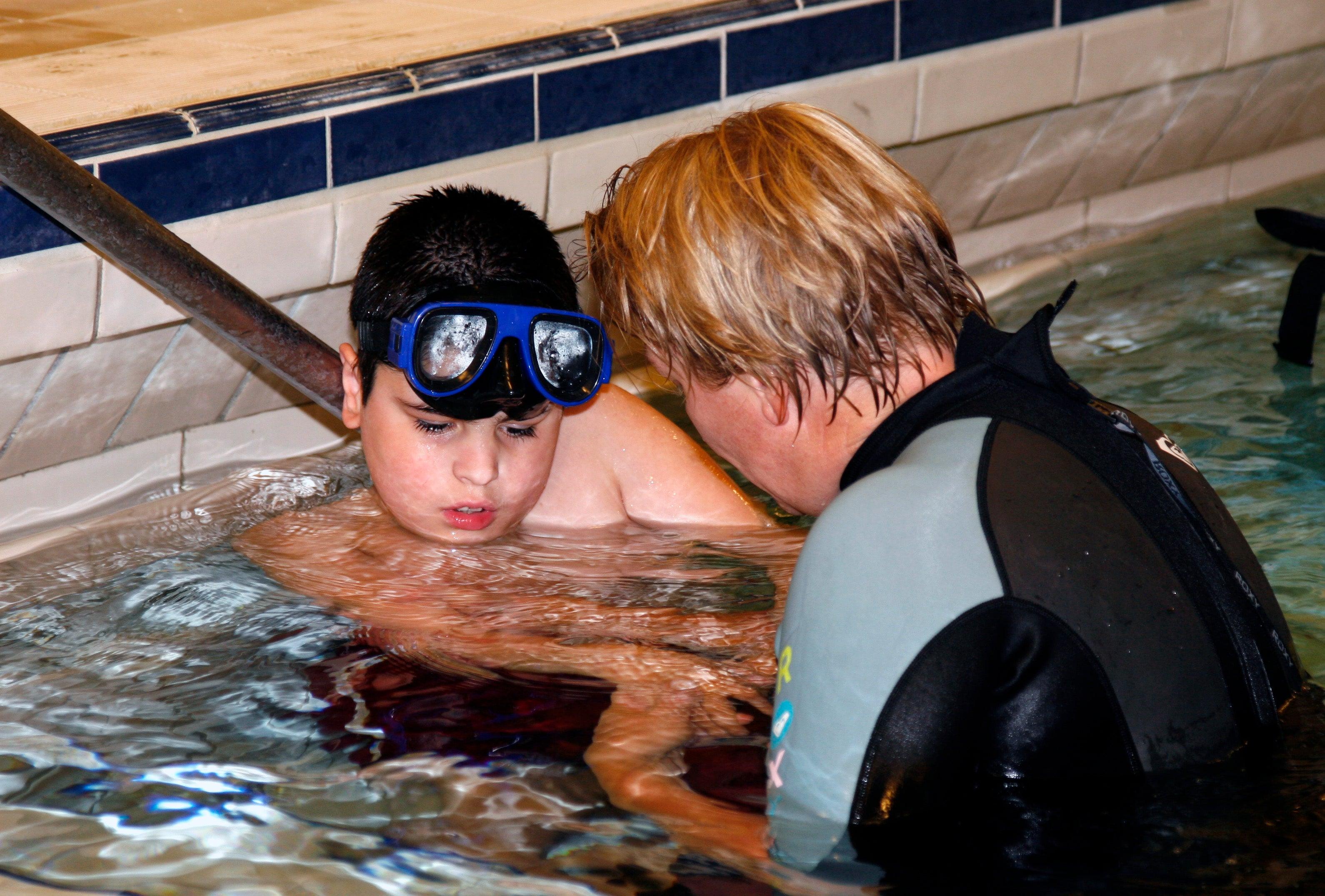 Jongen met duikbril krijgt zwemles