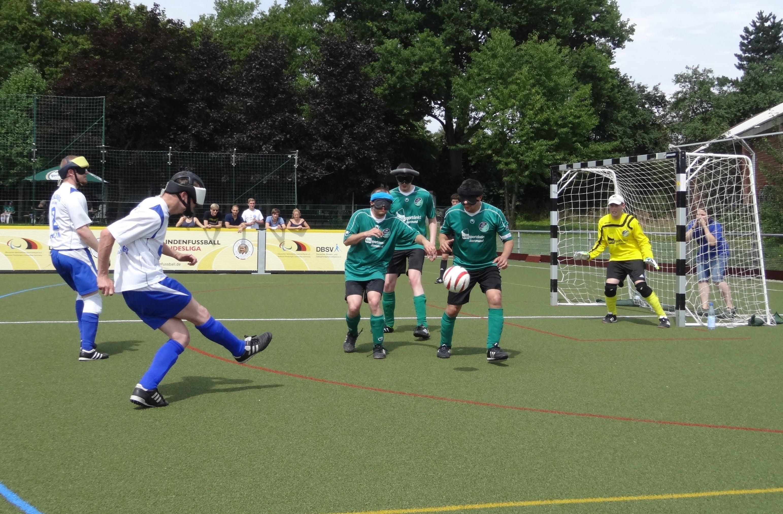 Twee teams met blinde voetballers aan de bal