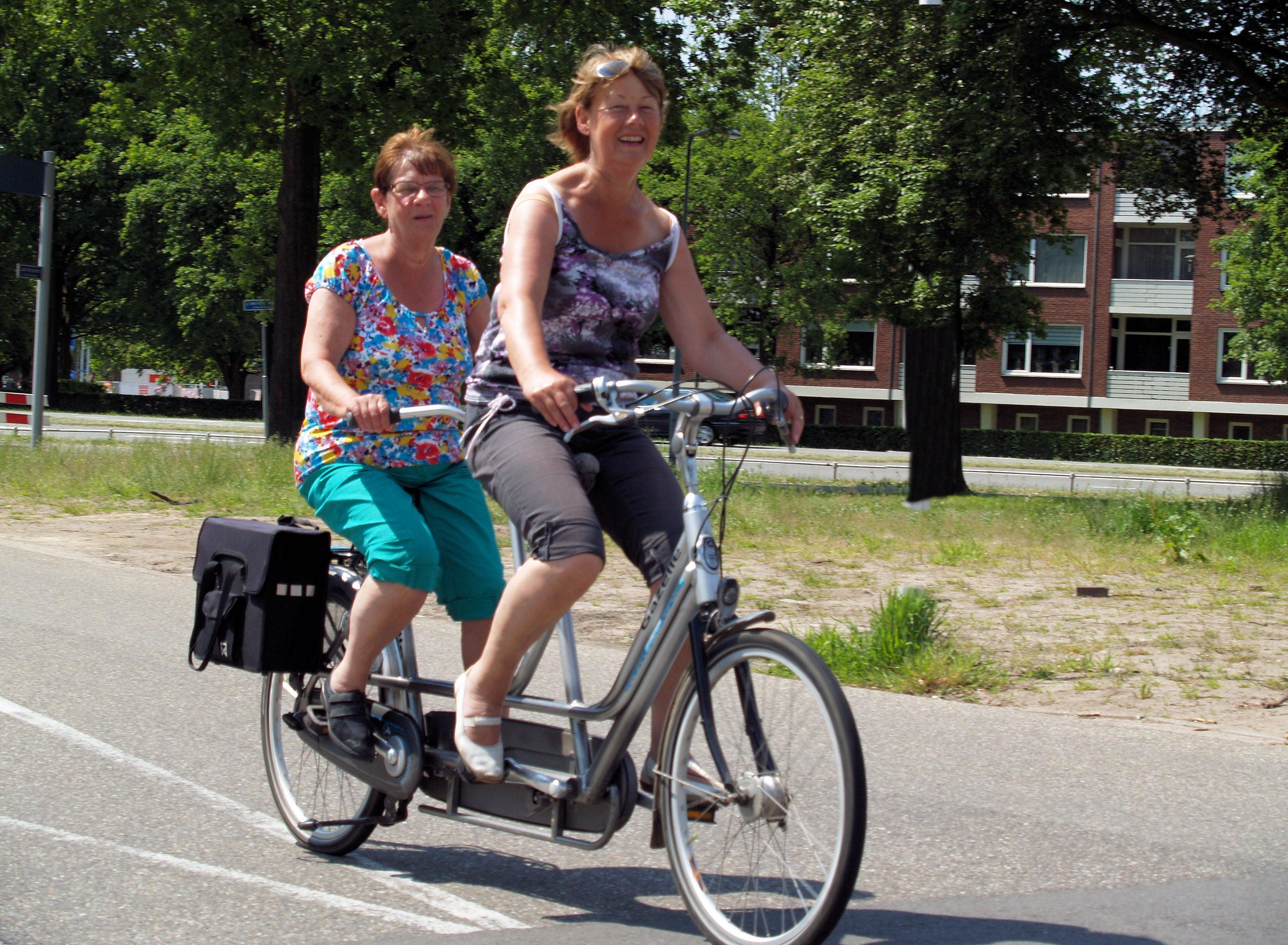Twee dames fietsen lachend op de tandem langs bomen en huizen.