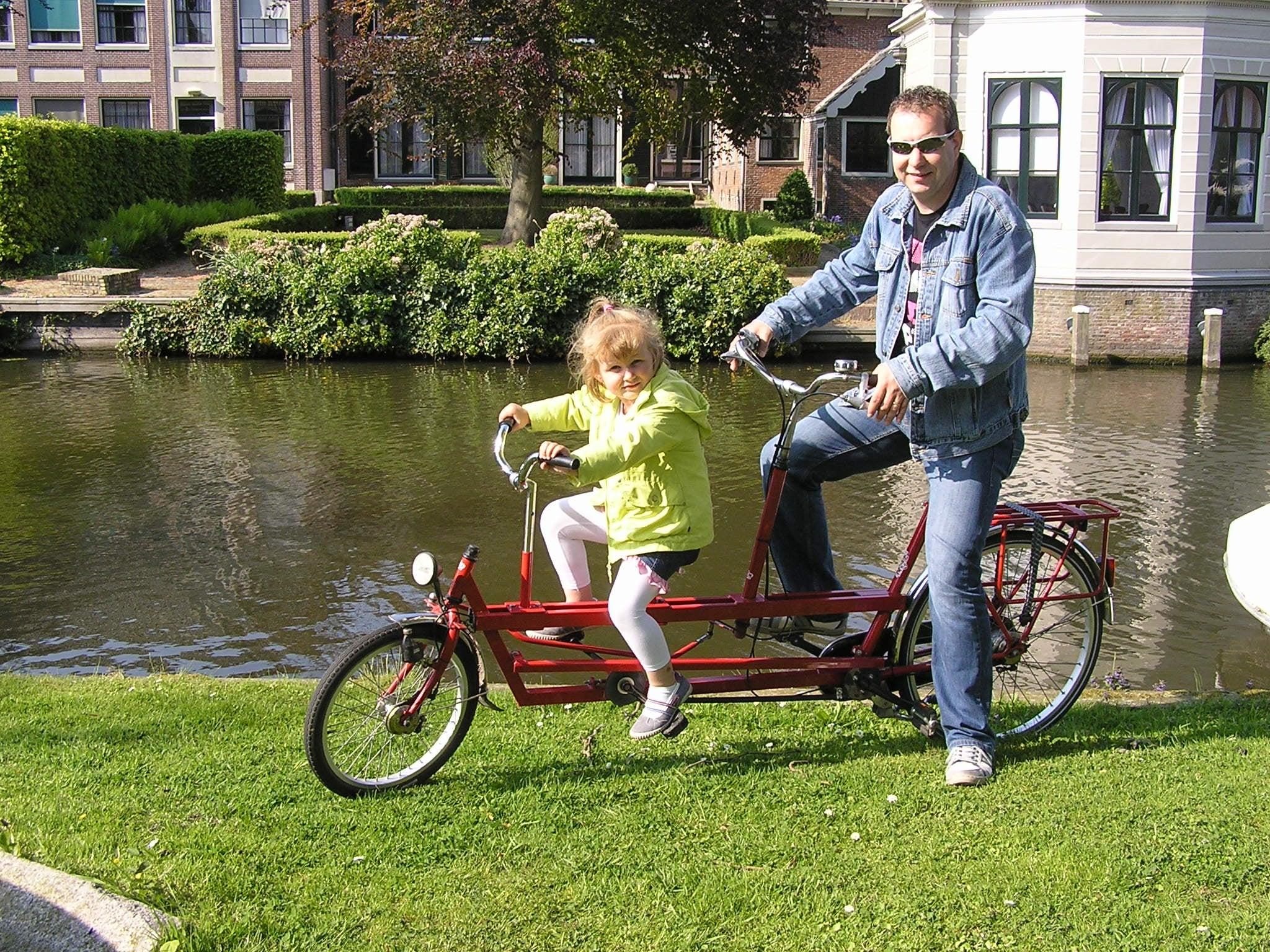 Vader en dochter op de rode nieuwe kindertandem.