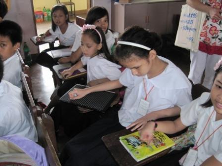 Klasje met leerlingen basisschool in de bank, daaronder een blind meisje met prikpen en reglette.