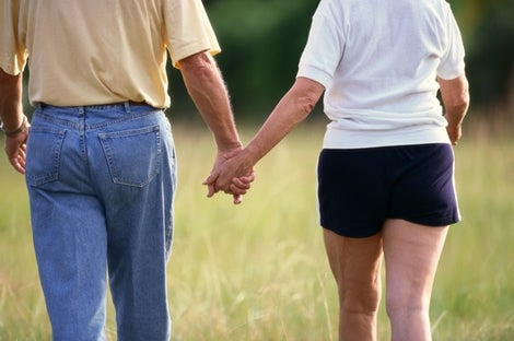 Image of man and woman holding hands and walking.