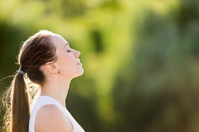 A young woman with her eyes closed raising her head toward the sky as if taking in a breathe of fresh air.