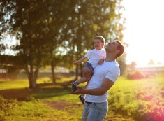 A man holds his young son while looking up at the sun.