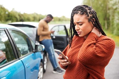 Black woman in organge sweater texts looking worried.