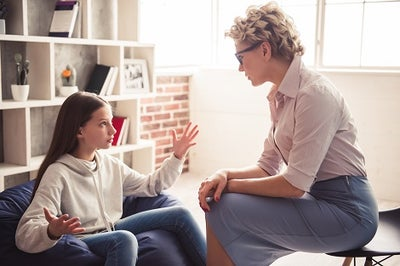 A teenage girl expressing with her hands held wide while talking to an adult female counselor.