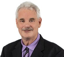 A man with gray hair, a mustache and wearing a purple shirt with a dark suit and tie.