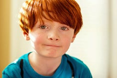 A young red-headed boy about 7 years old with hazel eyes looks directly at the camera with slight smile.