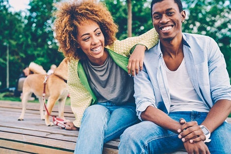 Young black couple, wearing blue jeans with their do on a leach are laughing while sitting on a wooden deck.