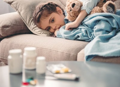 A young child lies under a blanket with a teddy bear looking at medications on the coffee table in front of her.