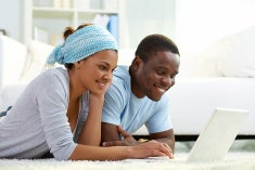 Two college aged African american people surfing the web on a laptop.