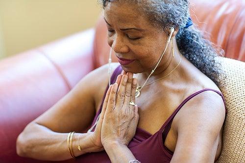 Black woman sits in pray hands meditating.