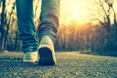 Someone's feet wearing sneakers while walking on pavement toward the sunrise.