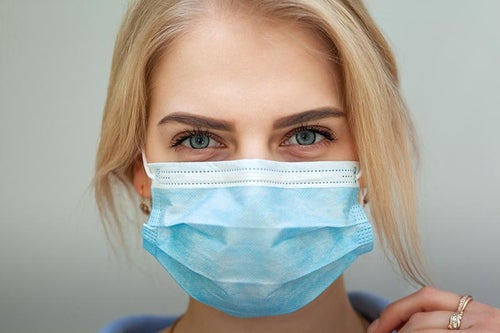 Woman with blonde hair wearing a clinical mask.