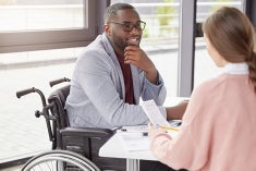 Man in wheelchair meeting with lady discussing notes.