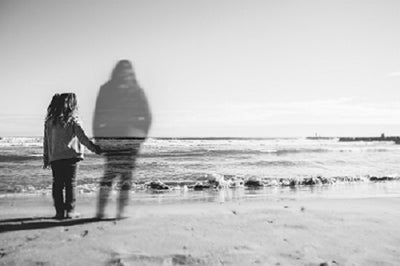 A young girl stands before the sea shore holding hands with the transparent, ghostly figure a deceased person who is dear to her. (a memory)
