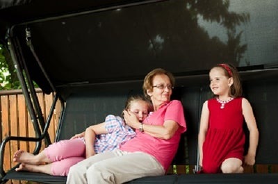 A woman of about 60 to 70 years old smiles at two young girls probably her granddaughters while sitting on a swing.
