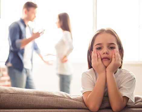 A young girl looks distraught while her parents argue in the background.