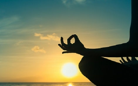 A silhouetteof a woman sitting cross legged with her wrists resting on her knees and fingers in the om position in front of a sunset.