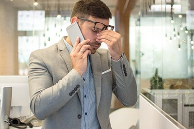 A business man pinches his nose while on the phone looking stressed.