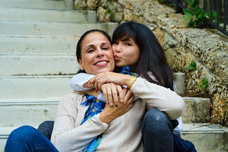 Hispanic young woman hugging an older women of similar ethnicity while sitting on steps.
