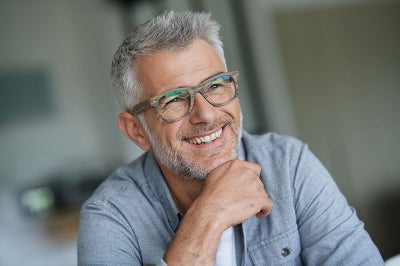 Gray haired white man with glasses smiles.